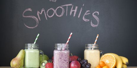 Still life of three fresh smoothies in front of blackboard