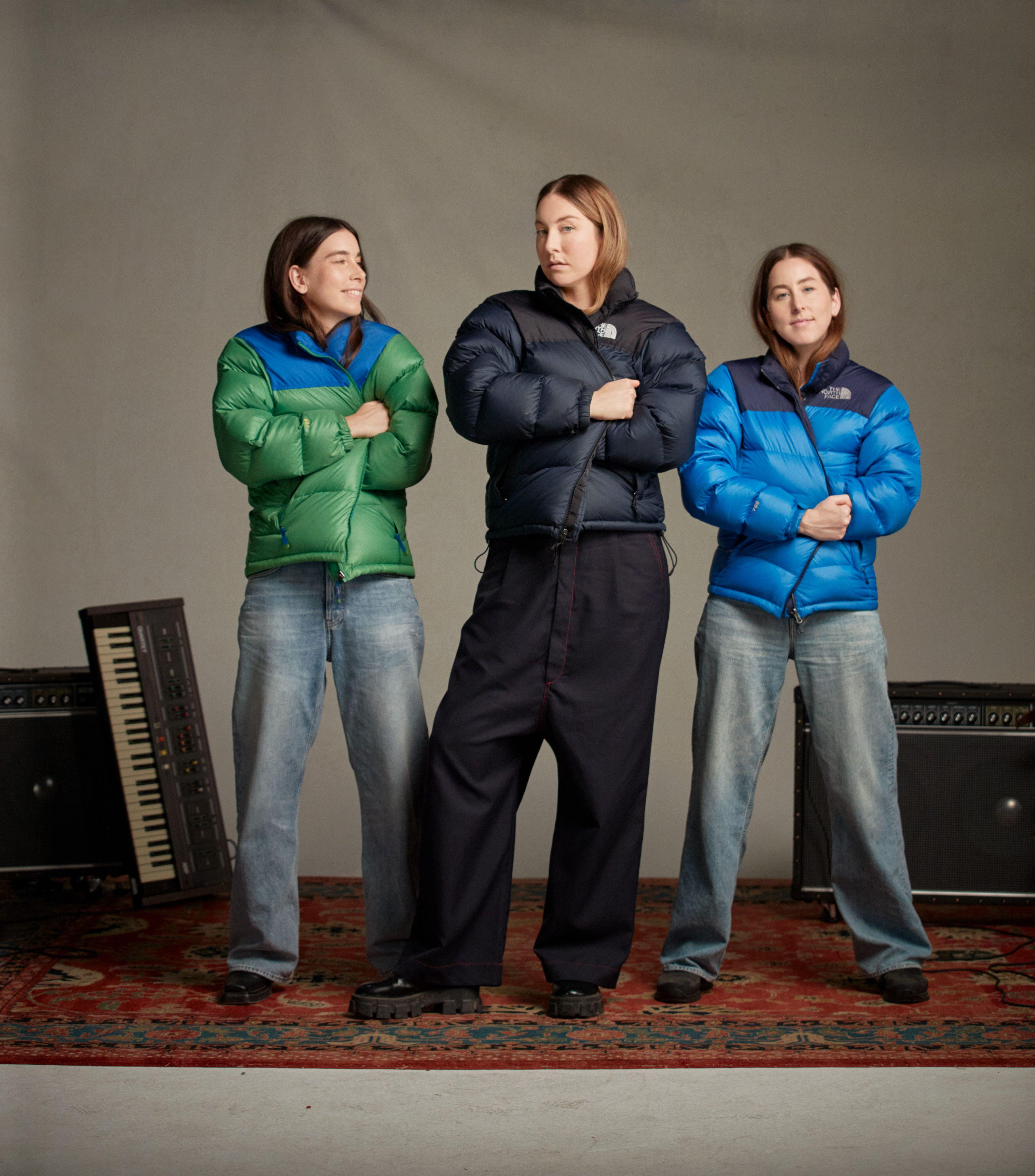 haim sisters posing in north face