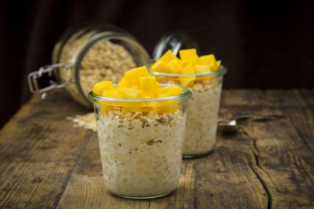 Two glasses of overnight oats with diced mango on wood