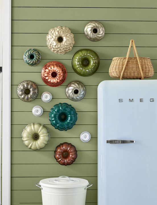 a collection of colorful bundt pans is hung in a kitchen
