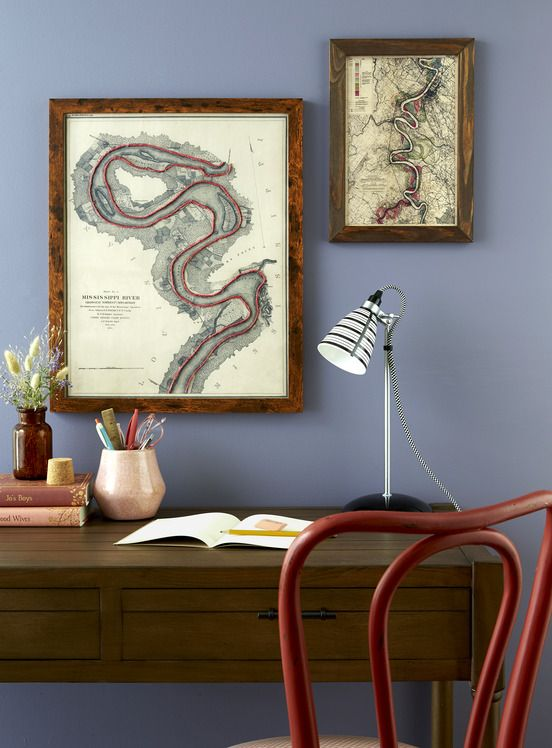 a pair of maps hang on a wall above a desk