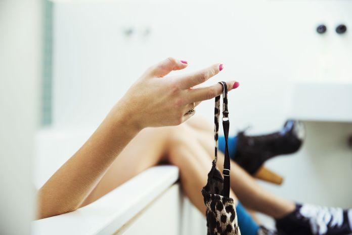 Woman removing bra in bathtub
