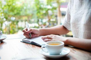drinking tea writing in journal