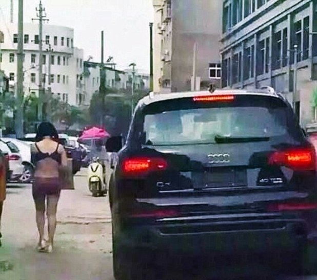 """Pic shows: The naked wife walking on the street. A man has penned an official apology to his local newspaper for drunkenly beating his wife and forcing her to parade through the city streets half naked after deciding she had been unfaithful. Wang Ni, 33, was seen wearing only her underwear while walking through traffic in Yushan County of southeast China's Jiangxi Province, and holding up a sign that read, """"I want to sell my body"""". Wang had allegedly been beaten by her husband Zhang, 37, after which she was forced to parade through the streets half naked. The husband was reportedly following her in his car to make sure she continued on the walk of shame. The couple have two daughters but the husband works long hours and has little time for their relationship, and even lives in another city where he runs a property development company. According to friends of the couple, he blamed his wife for the fact that despite 10 years of marriage she had given him two daughters and no sons - causing frequent rows that had split the family and meant that he often abused his wife on the few occasions when he did return home. But that abuse reached a new high when he returned home for a rare visit and decided to go out drinking with his friends who spread rumours that Wang was cheating on him with another man. Upon hearing the rumours, the drunken Zhang charged home and after beating Wang, and accusing her of being unfaithful, stripped her and forced her onto the streets with the sign. After police officers rescued the unfortunate woman and took her back to the police station, they called Zhang in for questioning. The result of the questioning was proof that the young woman had not been unfaithful and that her husband simply listened to malicious rumours with no foundation. Zhang later apologised to Wang and penned a formal apology in his local newspaper. It is not clear whether his wife has accepted his apology. (ends)"""