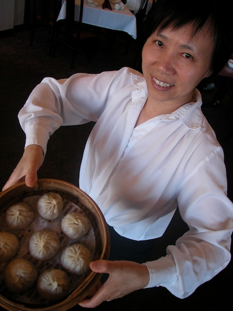 Yu Miao holds up a batch of freshly made deliciousness