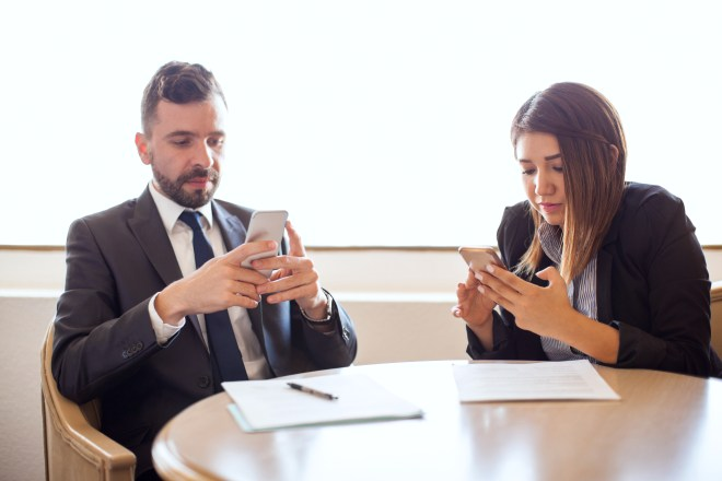 Business people distracted with their smartphones