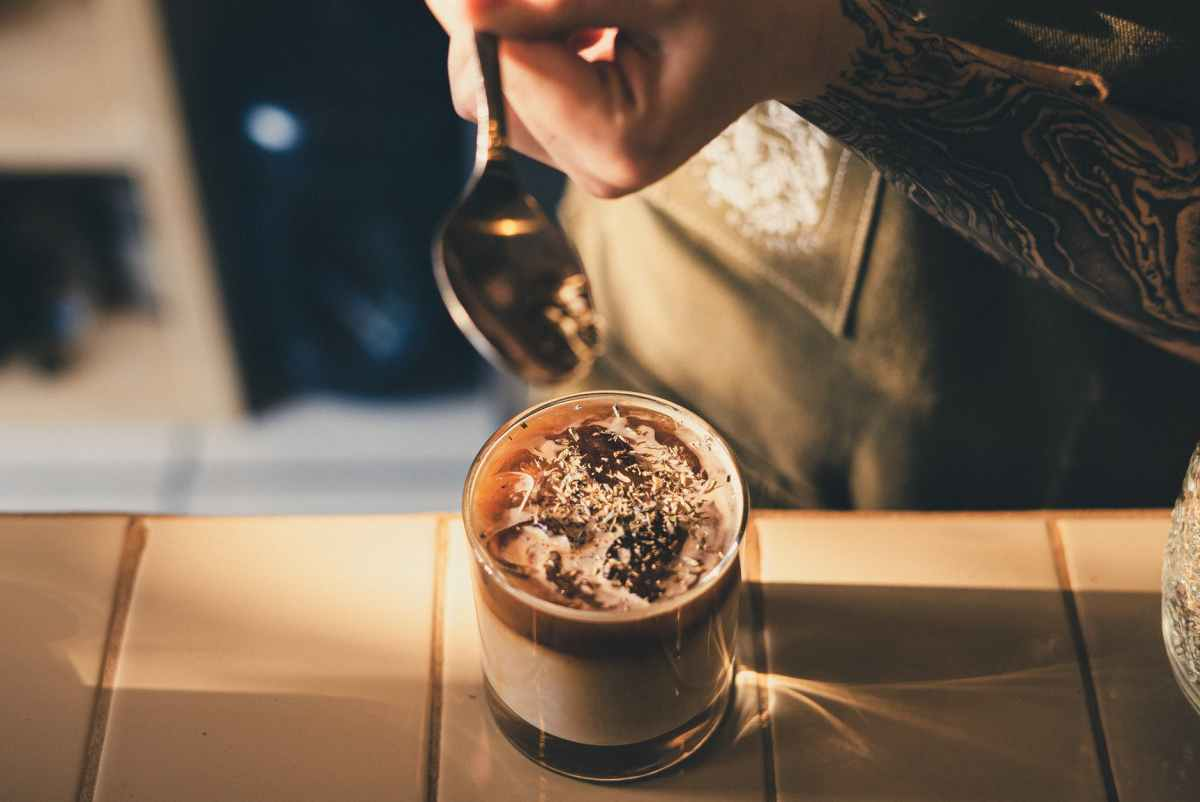 photo of barista holding stainless steel spoon