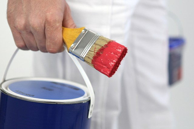 Painter/decorator carrying tins of paint and paintbrush