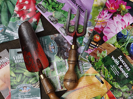 selection of seed packets and vintage garden tools