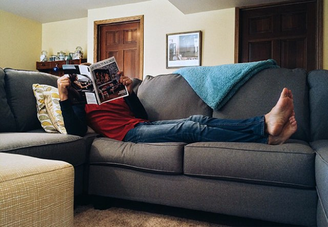Man reclining on a sofa reading a magazine