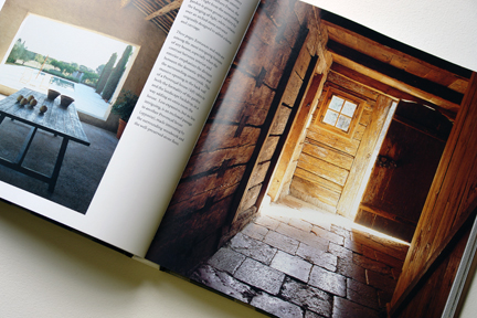 """double page spread showing an old stone flagged floor with sunlight streaming through from """"The Way We Live In the Country"""" by Stafford Cliff & Gilles de Chabaneix"""