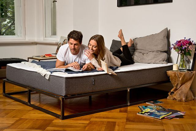 Couple laying on a Bruno mattress reading a magazine