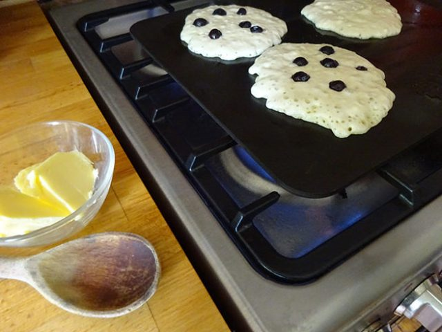 Frying buttermilk pancakes with blueberries on a stove-top griddle | H is for Home