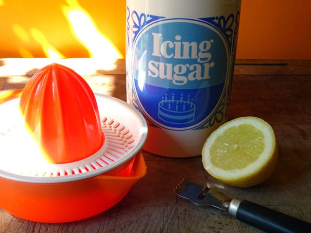 Slice of lemon, juicer, zester and icing sugar | H is for Home