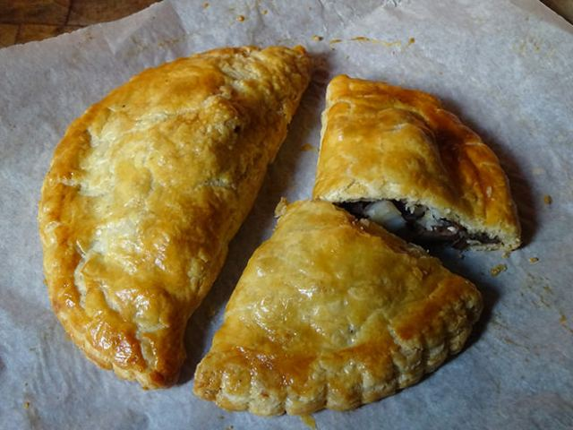 Two freshly-cooked mushroom pasties on parchment paper | H is for Home
