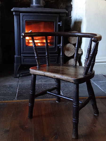 19th century child's chair in front of a wood burning stove