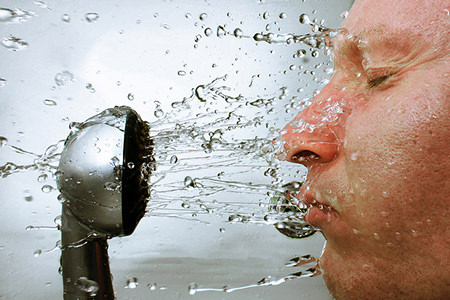 Man wetting his face with a shower head