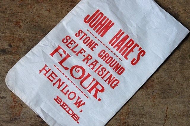Detail from a vintage John Hare's flour bag showing the red printed branding   H is for Home