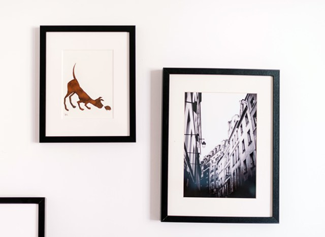 trio of framed artworks hung at different heights