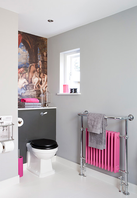 Bubble gum pink radiator, toilet brush holder and hand towel on a cloakroom