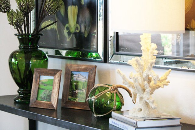 Mantlepiece decorated with emerald coloured glass, picture frames and coral-based lamp