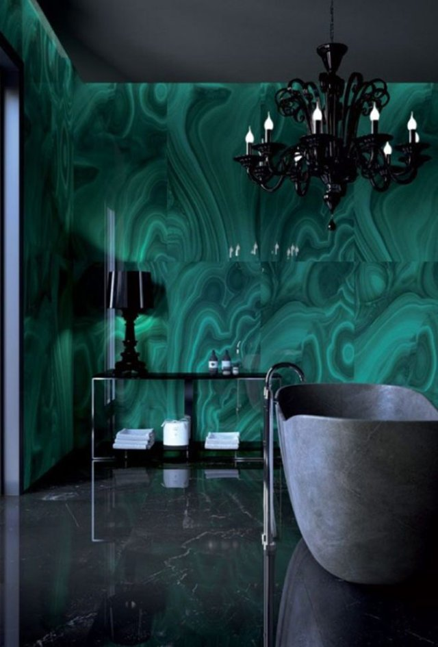 Bathroom with malachite wall tiles, concrete bath and black chandelier