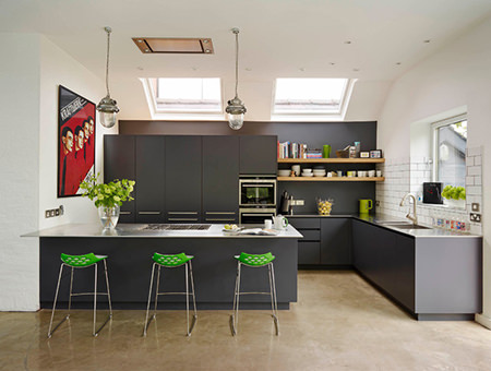 Nearly black fitted kitchen cabinets with contrasting lime green bar stools
