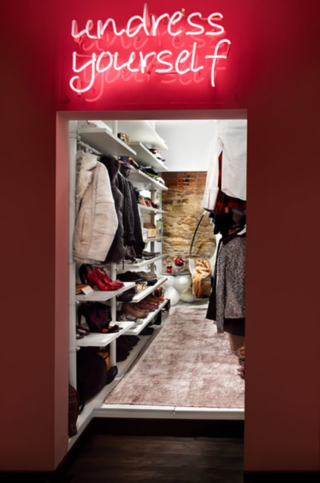 Red 'undress yourself' neon sign above the entrance to a walk-in wardrobe