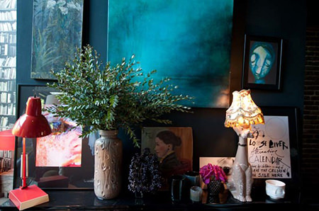 Petrol blue vignette containing artworks, lighting and vases