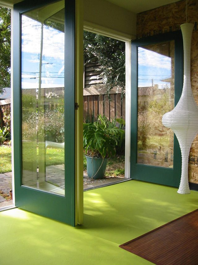Racing green coloured floor to ceiling folding doors out on to a garden