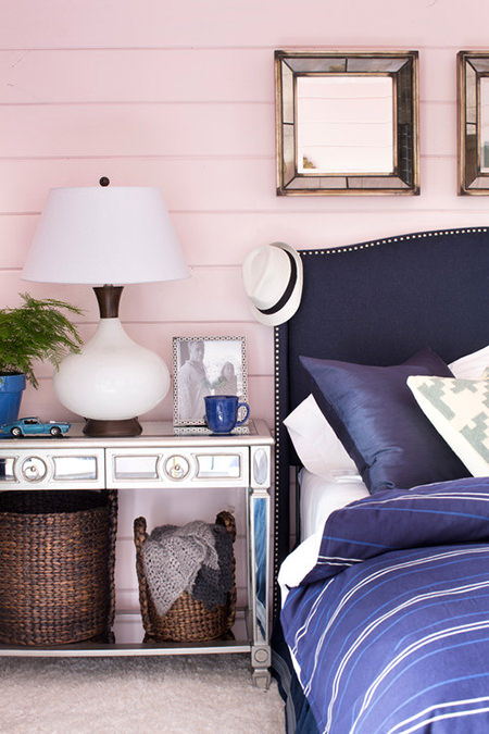 Rose quartz painted panelled wall with blue bed linen and headboard