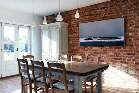 dining room with red brick wall with large painting of wooden spoons