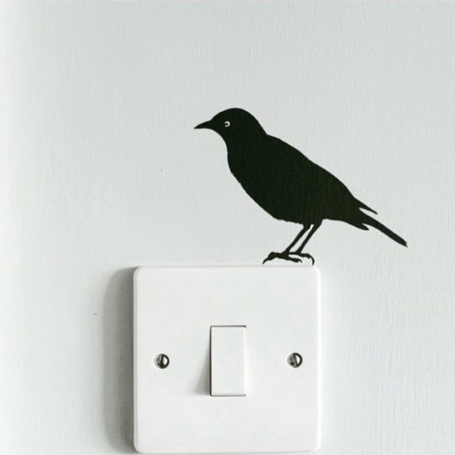 Crow vinyl sticker above a light switch