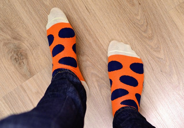 Feet in orange & blue spotted socks on a wooden floor
