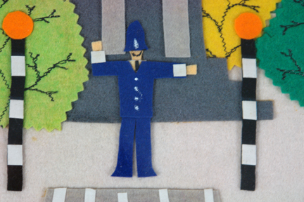 detail of felt artwork depicting a London policeman at a zebra crossing between a pair of Belisha beacons