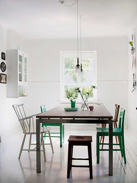 mismatched vintage chairs around a modern dining table