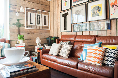 Tan vintage leather sofa with colourful modern cushions