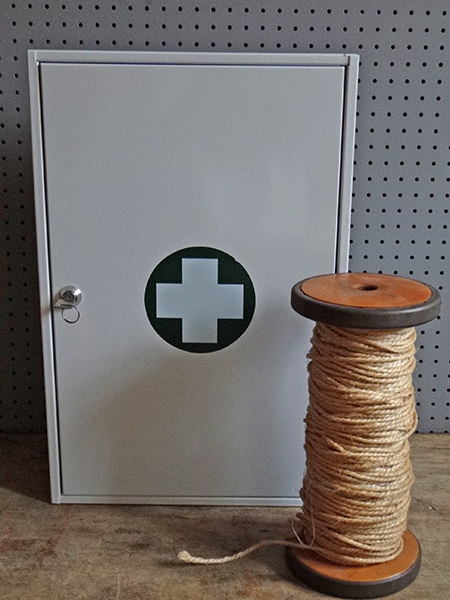 white first aid tin and wooden bobbin with jute twine