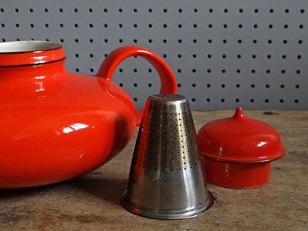 orange Rörstrand Pop teapot with lid off and strainer to the side