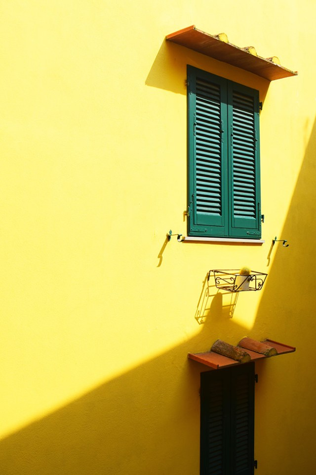 Green painted wooden shutters on a yellow house