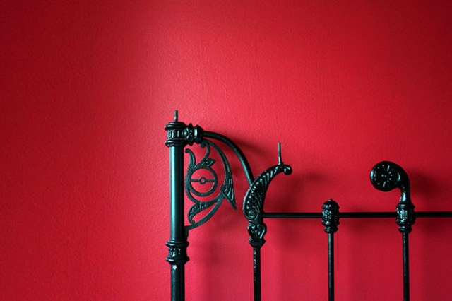 Bright red bedroom wall with black iron bed head