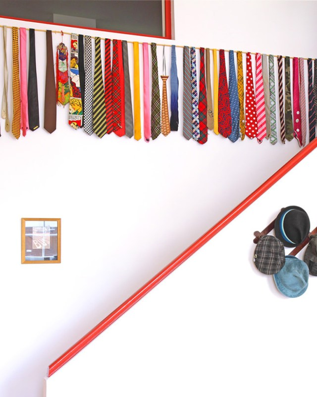 Collection of colourful neck ties hanging over a white-painted bannister