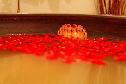 rose petals floating on bath water and feet with red-painted toe nails poking above the water
