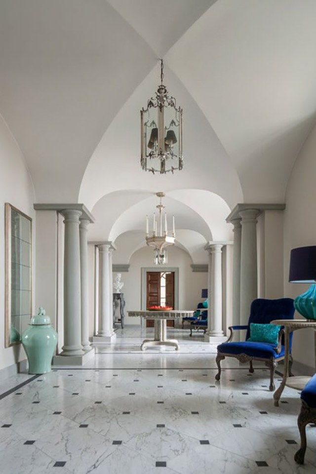 Marble floored hallway with bright blue furniture and accessories in a Tuscan villa