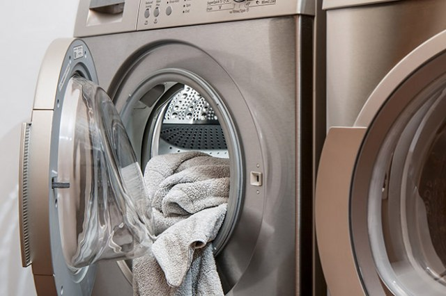 Silver coloured washing machine with towel