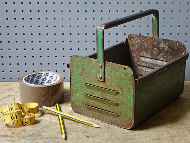 Green-painted vintage industrial carry box with packaging tape, measuring tape and pencils | H is for Home