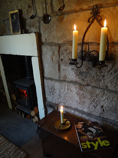 Lit Watts & Co church candle giving a warm glow to a stone wall