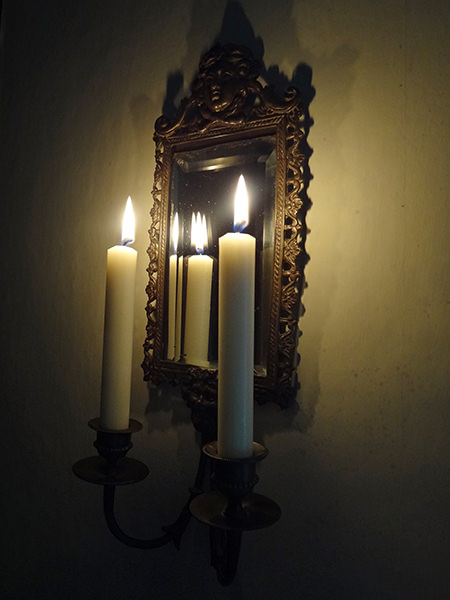 Lit Watts & Co church candles in an antique mirrored candle sconce