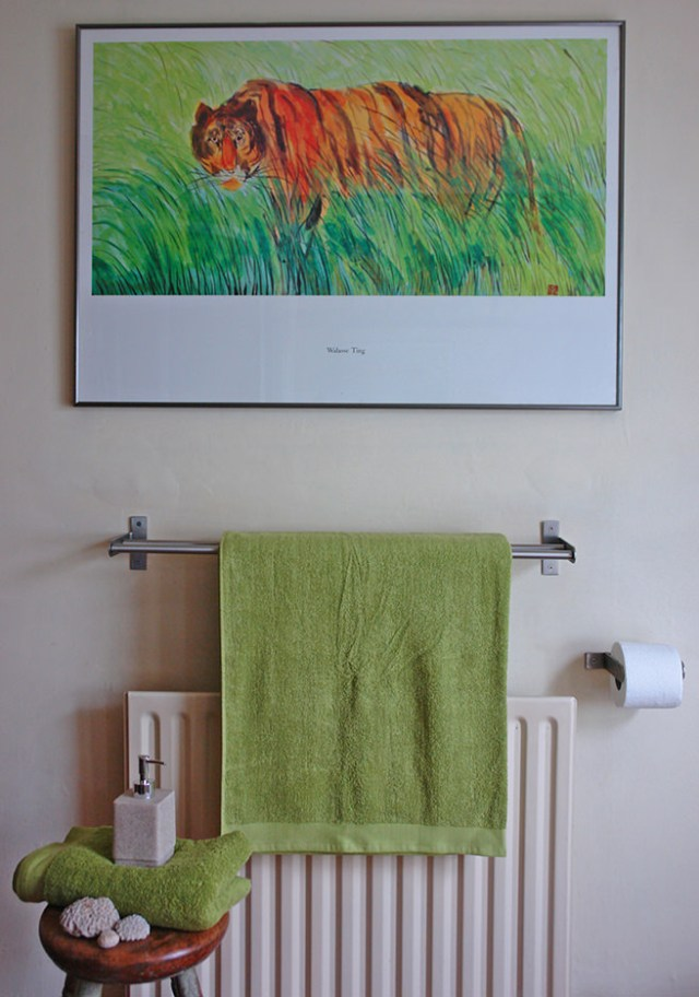 View of our bathroom with lime green towels and cream walls and accessories with colour coordinating print of a tiger in long grass | H is for Home