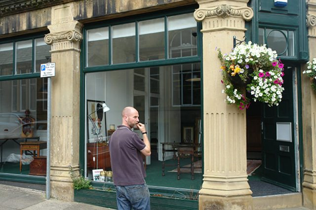Justin standing in the street outside our new shop space | H is for Home